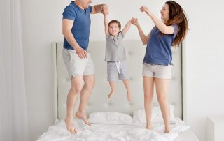 Family of three jumping on bed