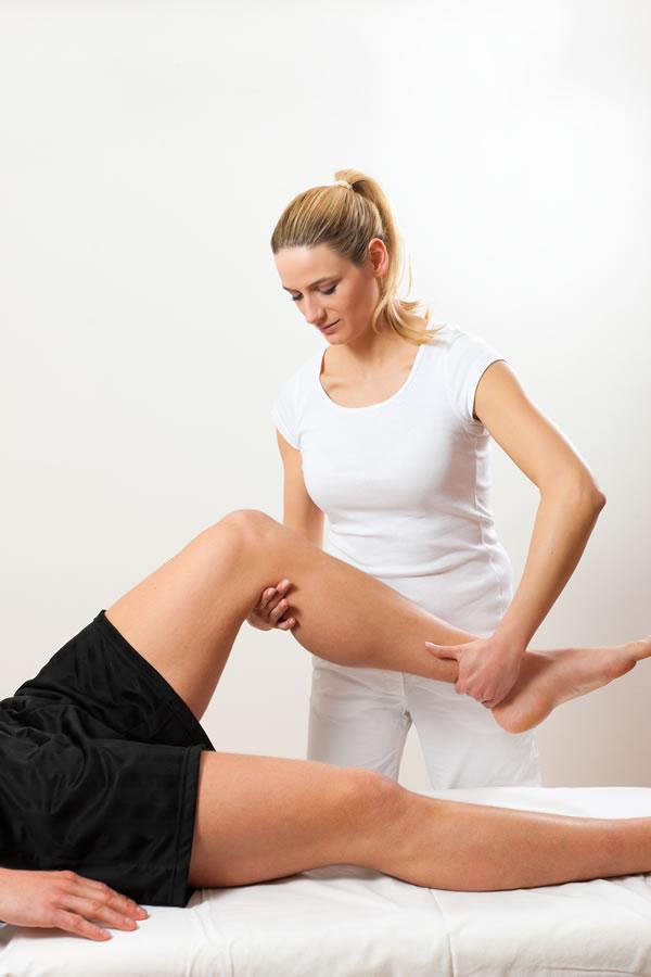 Massage therapist massaging mans leg