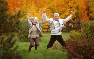 Elderly couple jumping among tress